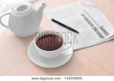 Cup of tea with newspaper on table