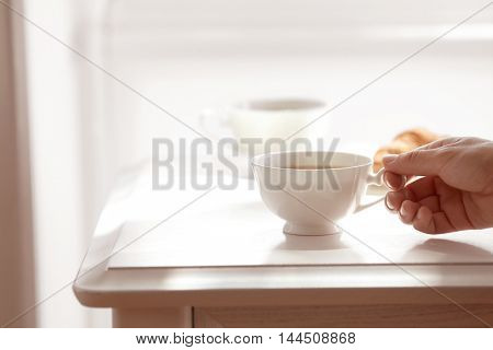 Female hand holding cup of tea on table