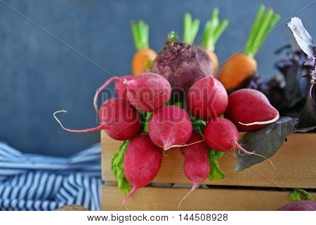 Crate with vegetables on wall background