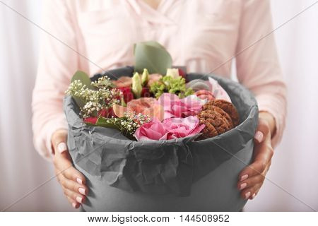 Female hands holding gift box with flowers and cookies closeup