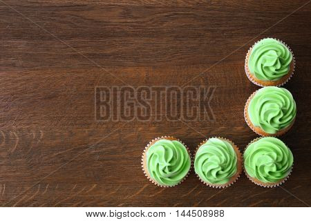 Tasty cupcakes on wooden background.