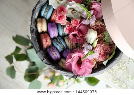 Box with fresh flowers and macaroons on light background, top view