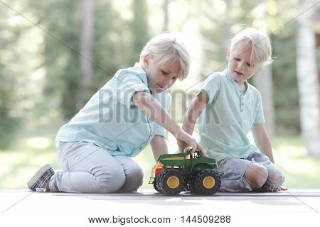 Little brothers playing with toy cars outdoors