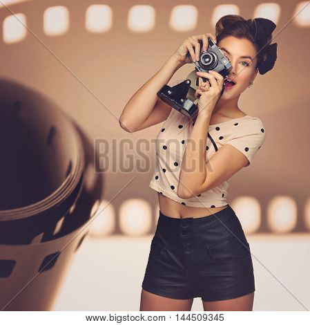 Happy beautiful young woman taking picture with retro photo camera. Surprised expression. Film background.