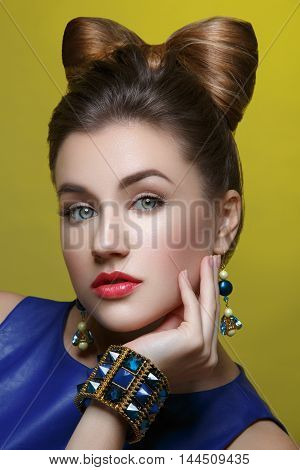 Beautiful young woman in blue dress with makeup and hair bow style on head. Studio shot over green background.