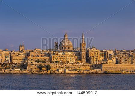 Valletta Malta - The famous St.Paul's Cathedral and the ancient city of Valletta at sunset with clear blue sky