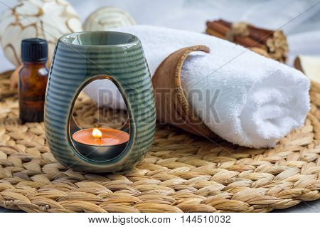 Aroma lamp with grapefruit essential oil on woven mat spa background horizontal