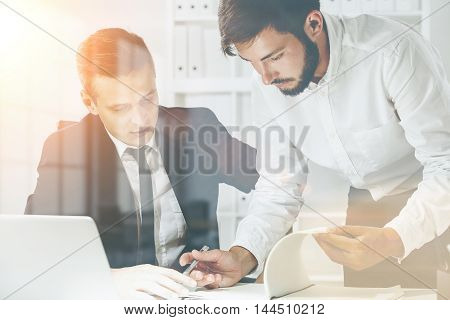 Two men in formal clothes working together in office with laptop and bookshelves with binders. Concept of cooperation. Toned image