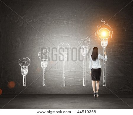 Business lady lightning torch with light bulb. Blackboard background. Concept of inspiration and creativity