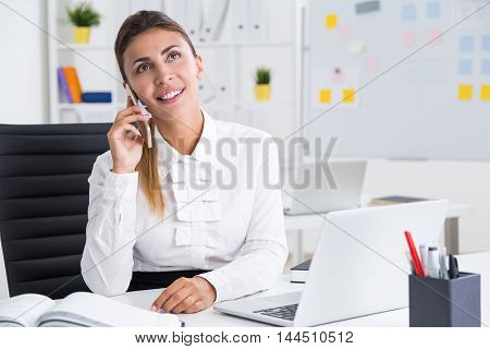 Dreamy business lady talking on her cell phone while sitting at office with white laptop and bookcase. Concept of vacation planning