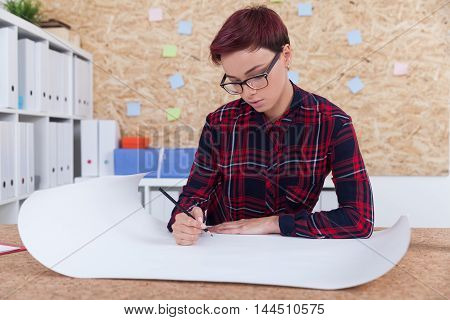 Woman architect drawing blueprint in her office. Shelves with binders and cork board with sticky notes in background. Concept of engineering