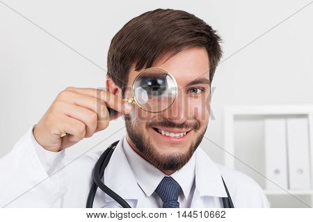Smiling doctor with stethoscope in white gown looking through magnifying glass. Concept of forensic work