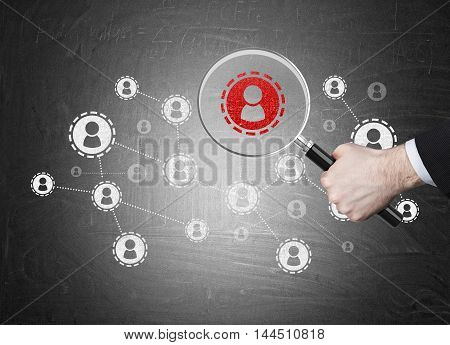 White and red startup sketch on blackboard. Man's hand in suit holding magnifier above red icon. Concept of recruiting