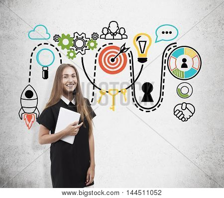 Smiling young business lady standing near concrete wall with colorful startup sketches. Concept of brainstorm