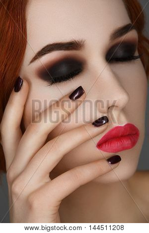 Beautiful young woman with smoky eyes and full red lips. Hands with dark nail polish. Studio beauty shot over blue background. Copy space.