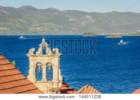 View at bell tower of Church of All Saints in town Korcula with marble archipelago in background, Adriatic sea, Croatia.