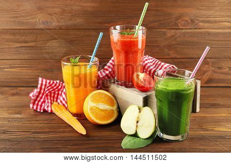 Tasty smoothie drinks with vegetables and fruits on table