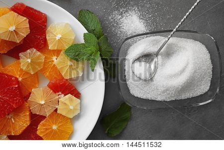 Plate with different citrus slices and sugar in glass bowl on grey background