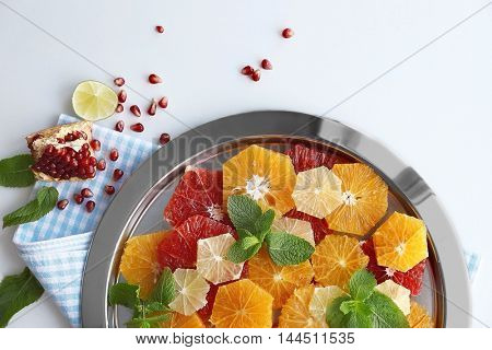 Plate with different citrus slices on light background