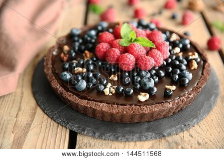 Delicious chocolate tart with berries and nuts on slate plate, closeup