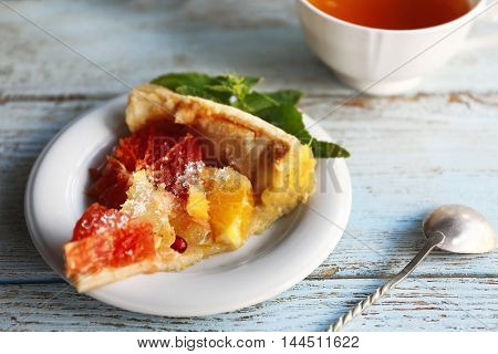 Plate with tasty citrus cake slice on wooden table