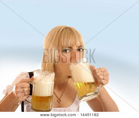 Attractive bavarian woman drinking beer  over blue background