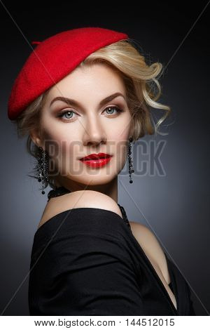 Beautiful lady in red beret. Beauty portrait. Red lips. Over black background.