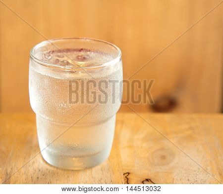 Glass off water placed on wooden table.