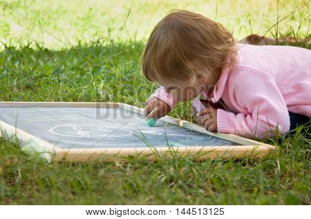 little girl draws with chalk on the board on the nature