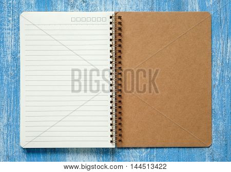 white and Brown notebook on blue wooden floor.
