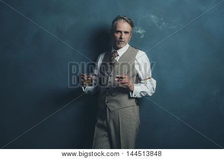 Retro Businessman 1920S Style Smoking Cigar And Holding Glass Of Whiskey. Leaning Against Wall.