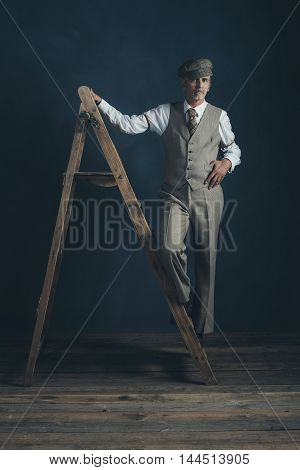 Vintage 1920S Man In Suit Standing On Old Wooden Ladder In Empty Room.