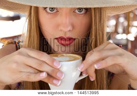 beautiful woman in hat holding a cup of delicious hot coffee