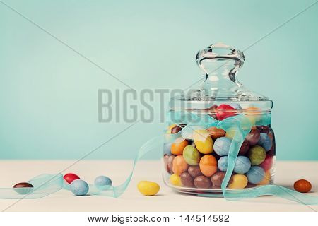 Colorful candy jar decorated with bow ribbon against blue background for Birthday or Easter holidays.