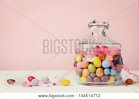 Colorful candy jar decorated with bow ribbon against pink background. Gift or present for Birthday or Easter.