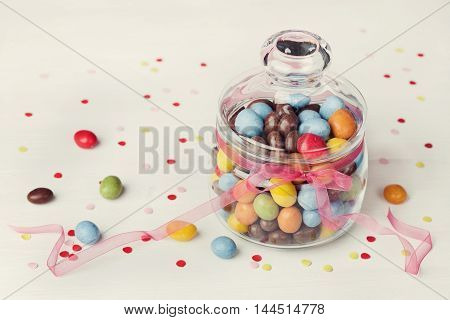 Colorful candy jar decorated with bow ribbon on white background with confetti. Gifts for Birthday or Easter.