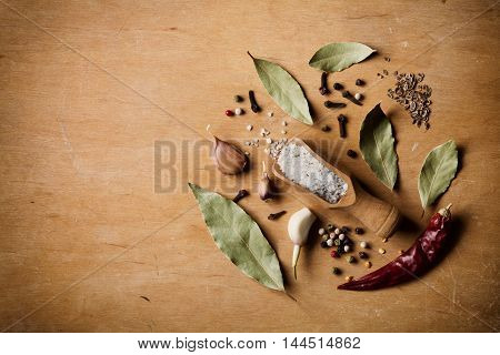 Dry ingredients for cooking on wooden table. Sea salt, garlic, bay leaf, pepper and clove top view. Rustic style.
