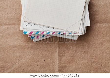 Stack of old envelopes and letters on kraft paper, top view.