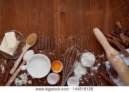 Ingredients for baking dough including flour, eggs, milk, butter, sugar, cinnamon, anise star, whisk and rolling pin on wooden rustic background. Empty space for text. Top view. Flat lay.