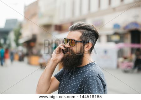 handsome sexy bearded young man hipster with long beard and mustache has stylish hair on smiling hairy face in sun glasses speaking on mobile phone outdoor closeup