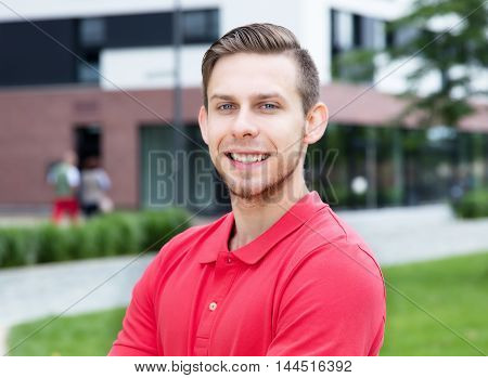 Caucasian male student with stubble looking at camera outdoor on campus