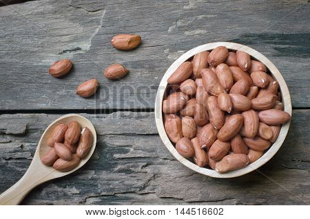 Peanuts in wooden bowl and wooden spoon on wooden table background