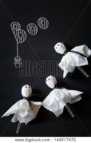 Halloween ghost lolly pops on black chalkboard.