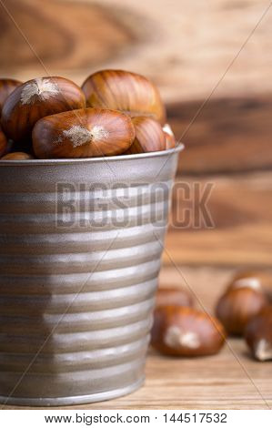 chestnuts in a tin bucket and chestnuts on wood