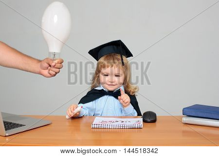 Little boy child smiling in black academic mantle and squared cap sitting at school wooden desk holding mark near notebook computer mouse and diaries on background of male hand with light bulb