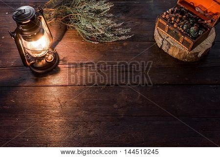 Old-fashioned kerosene lamp and chest of jewelry on the dark table in twilight. Soft focus