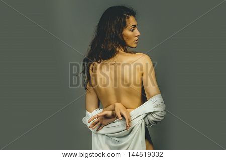 young pretty woman with long brunette curly hair in white shirt has slim sexy body standing with back in studio on grey background copy space