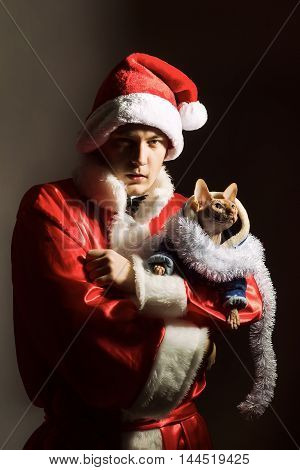 young man in red and white santa claus coat and hat at christmas or new year winter holiday holding sphinx cat on hands
