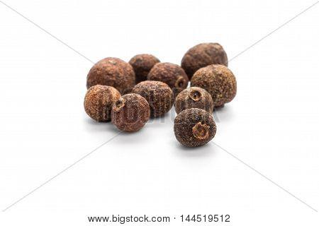 Whole allspice grains isolated over white background
