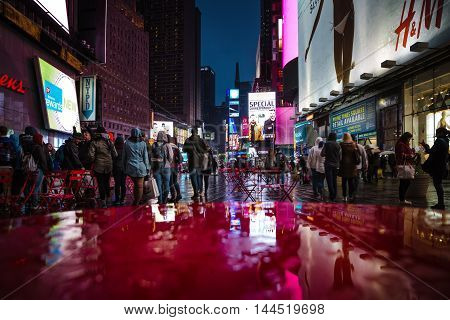 NEW YORK USA - Apr 30 2016: Lights and shadows of New York City. NYC streets after rain with reflections on wet asphalt. Silhouettes of people walking on the street